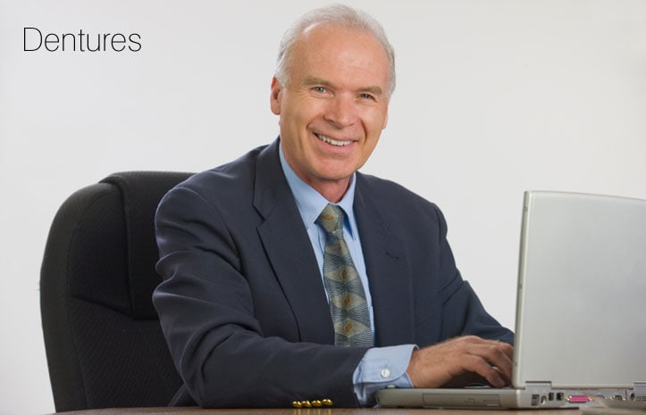 Man in suit smiling with his dentures in