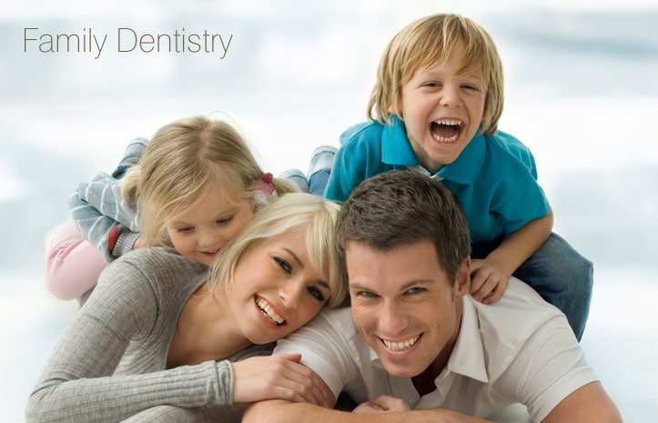Family of four smiling after getting their teeth cleaned at the family dentist office