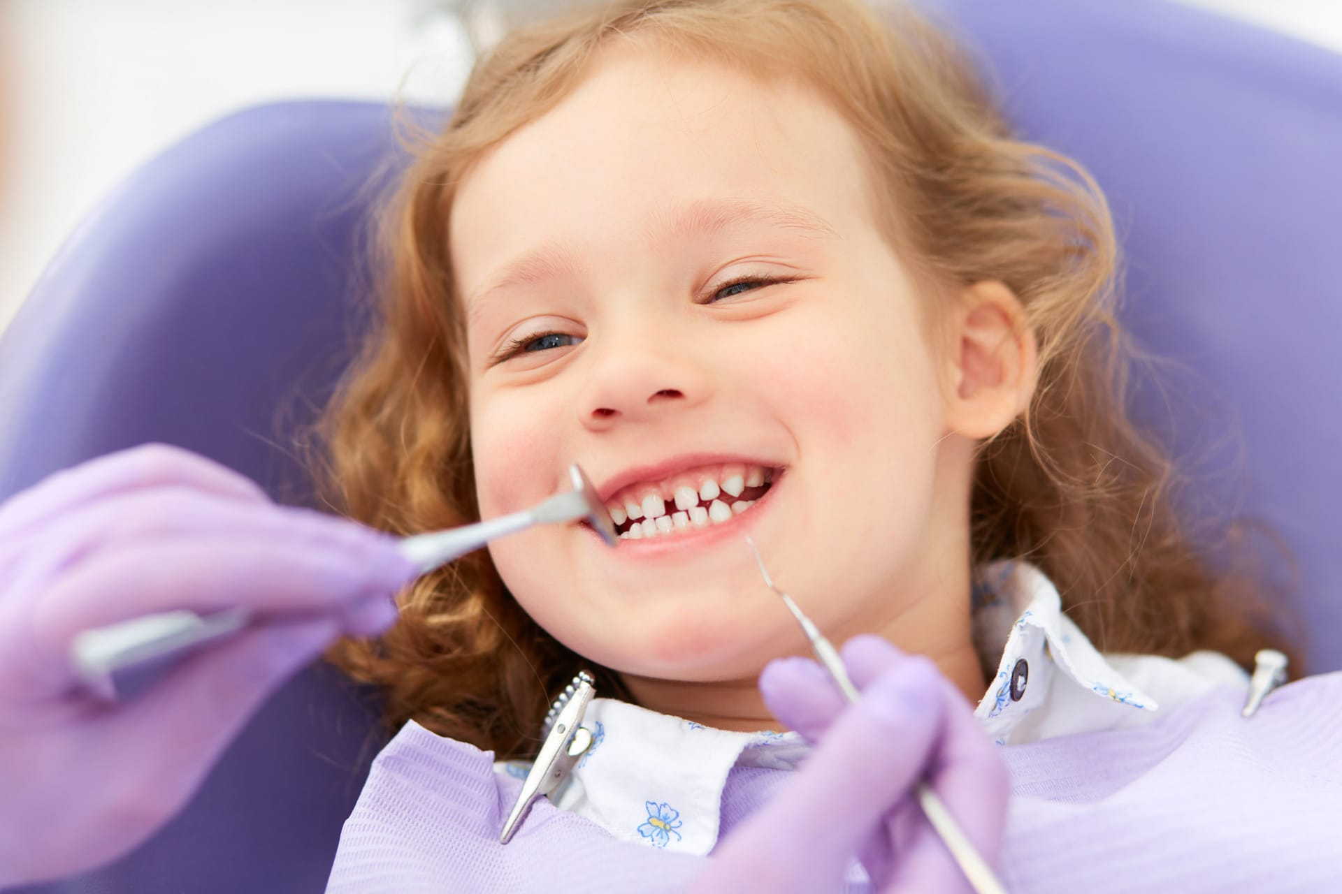 pediatric dentist with a kid in the dentist chair